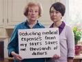 Dos mujeres y una sostiene una pancarta con un mensaje sobre la reforma sobre impuestos