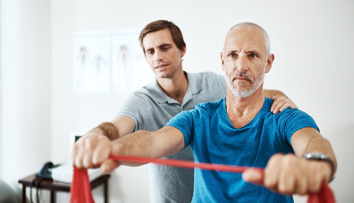 physical therapist helping older man stretch