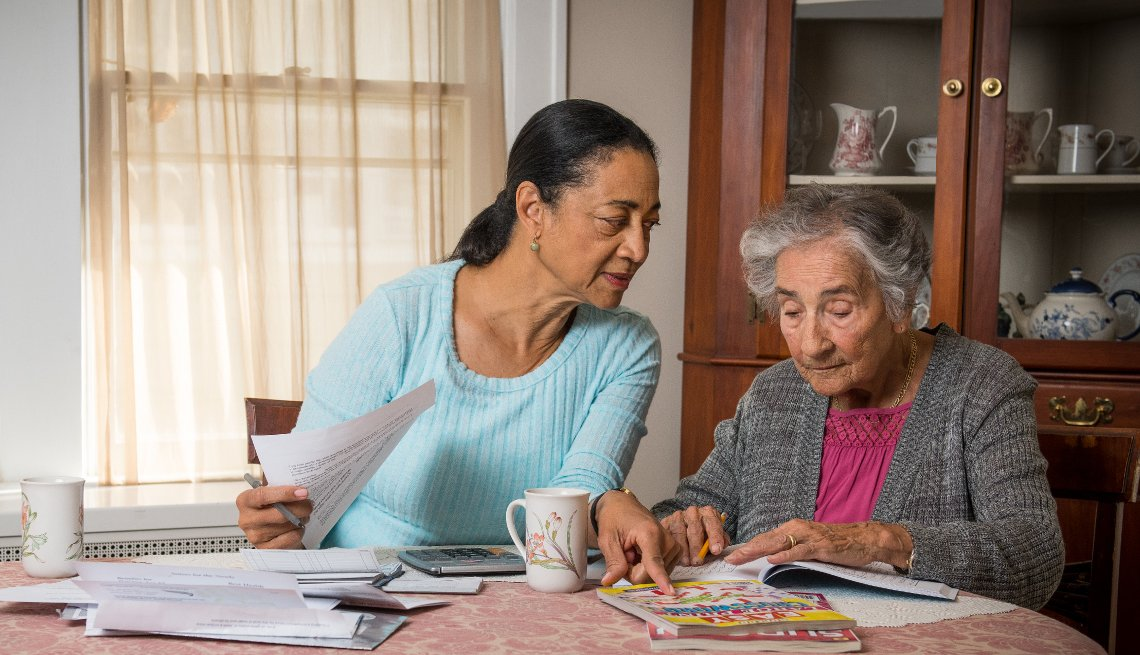 caregiver helps an older woman with paperwork