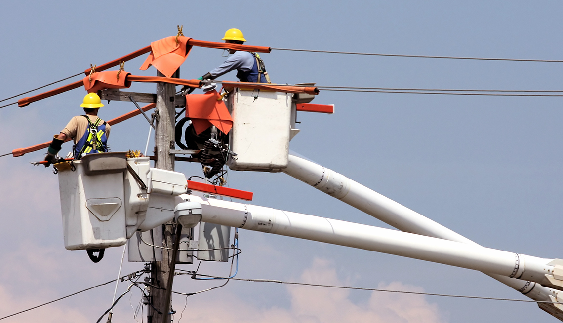 Two utility workers in a crane repairing a power pole