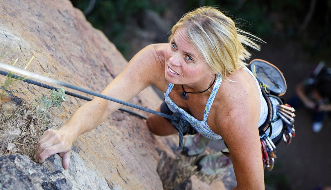 A middle-aged woman rock climber climbing a rock feature, Disrupt Aging AARP