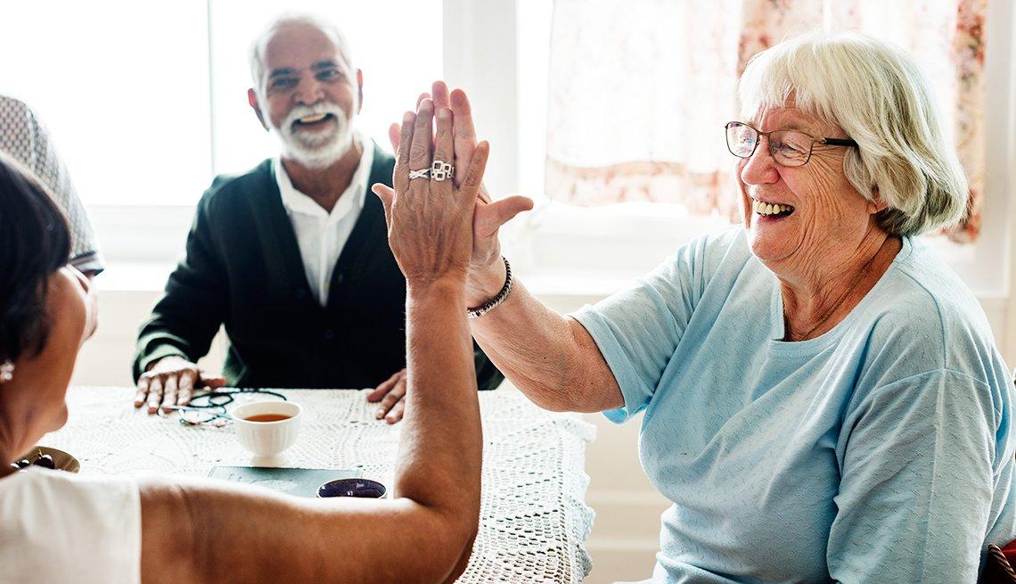 Dos mujeres mayores sonríen mientras se chocan las manos.