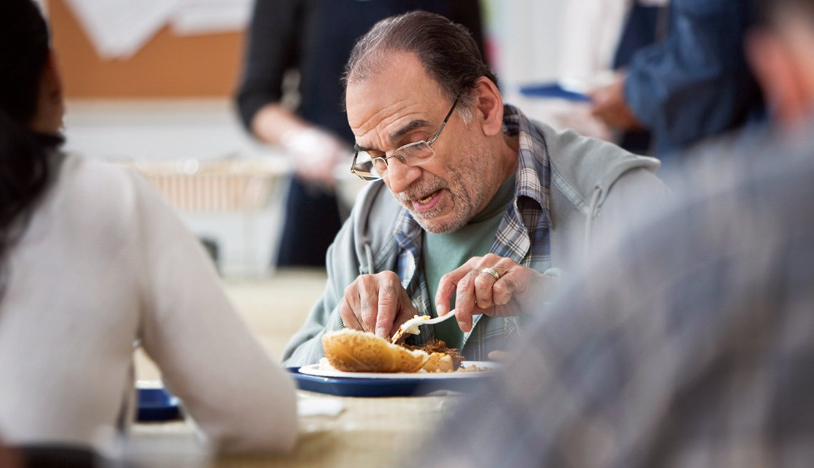 mature man eats in a soup kitchen