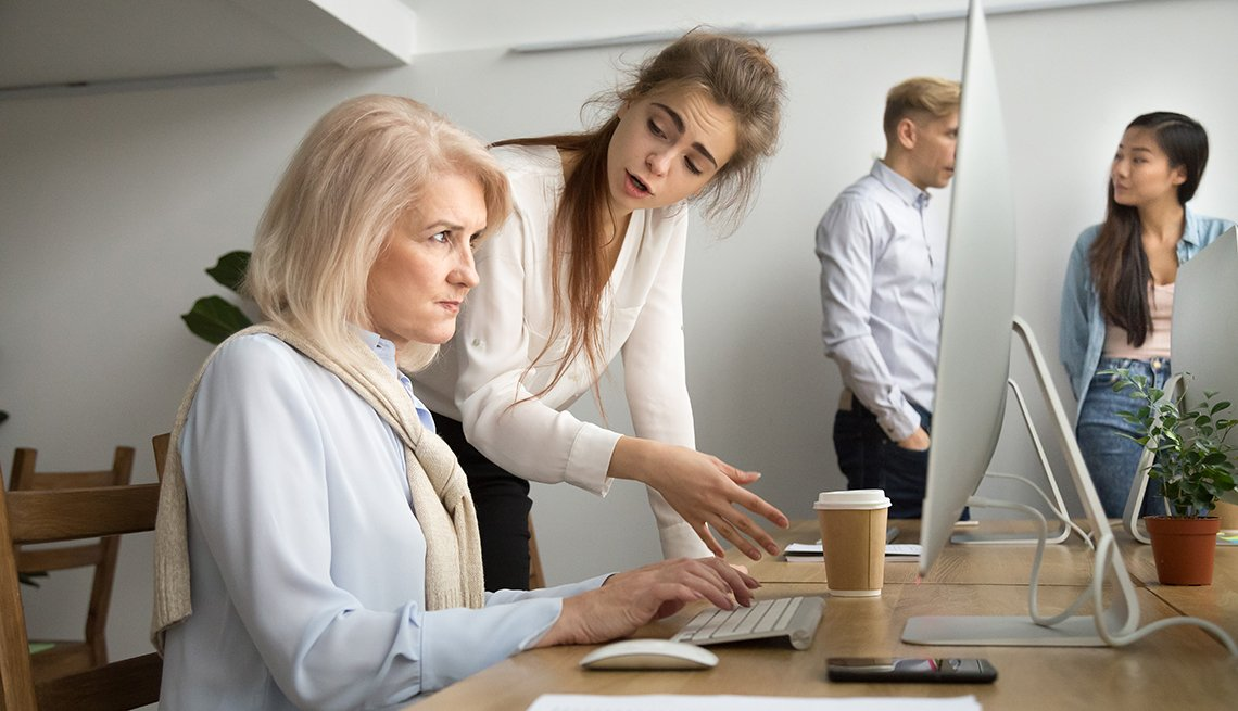 A woman working at a computer being scolded by a younger worker.