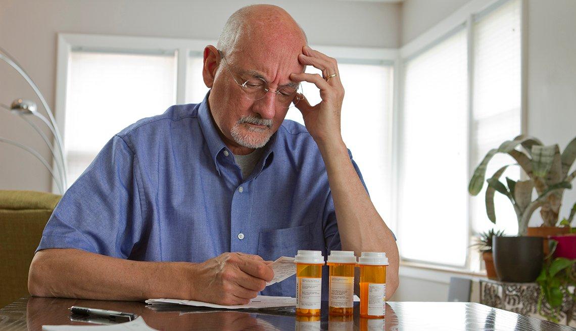 Hombre sentado en una mesa, con tres recipientes de medicinas, mira un papel.
