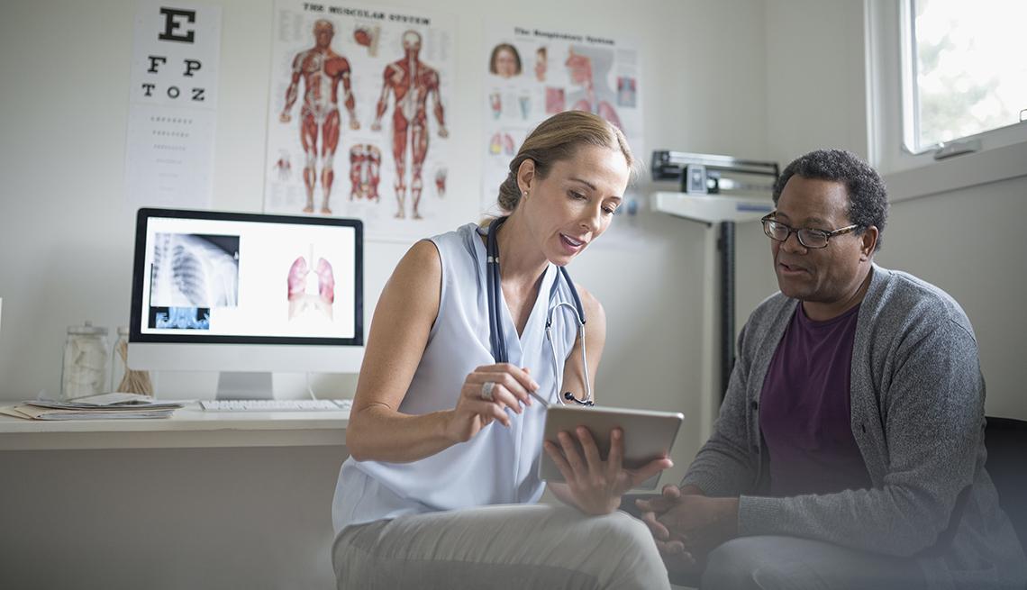 Doctora con tableta digital habla con un paciente masculino mayor en su consultorio.