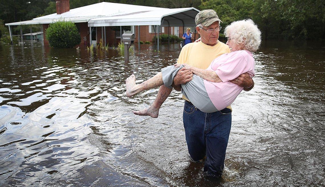 Man rescuing an older woman during Hurricane Florence.