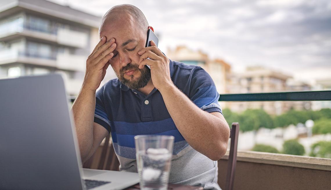 Hombre sentado frente a su computador habla por teléfono.