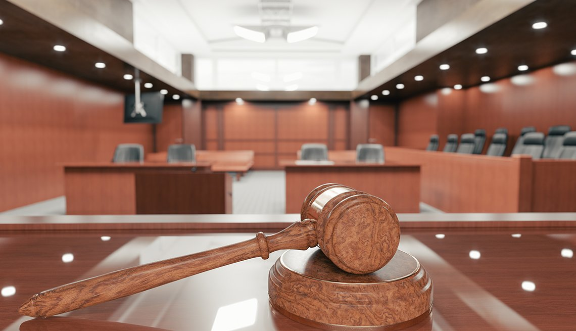 Interior de una corte judicial vacía con martillo de madera sobre el escritorio.