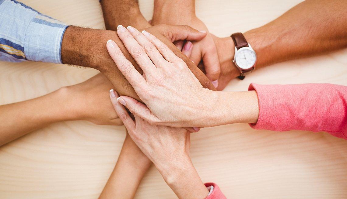 Empresarios poniendo sus manos juntas sobre la mesa.