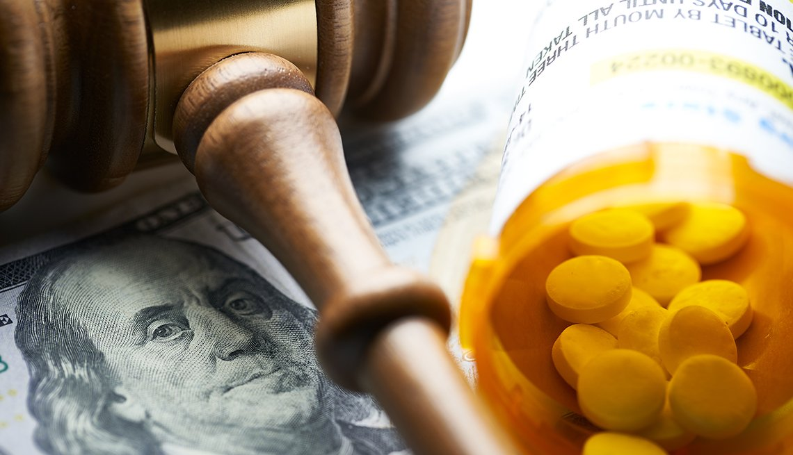 A gavel on top of money and a pill bottle