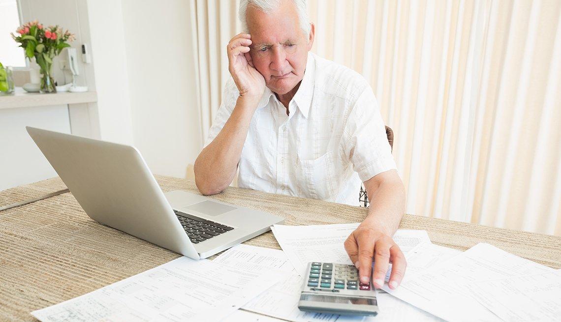 Hombre en frente de su computadora usa una calculadora
