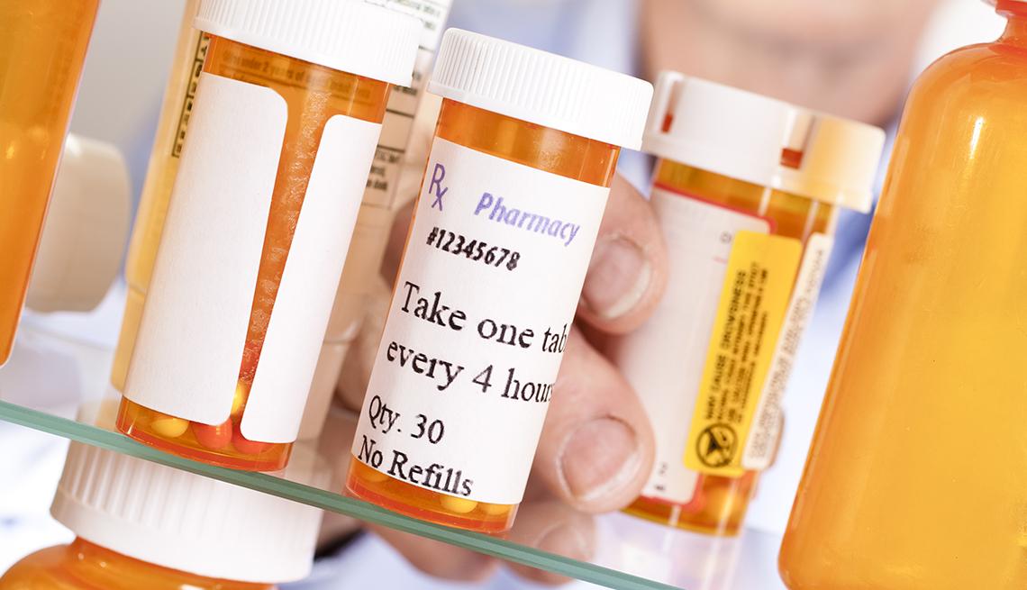 Hombre saca sus medicinas de un gabinete