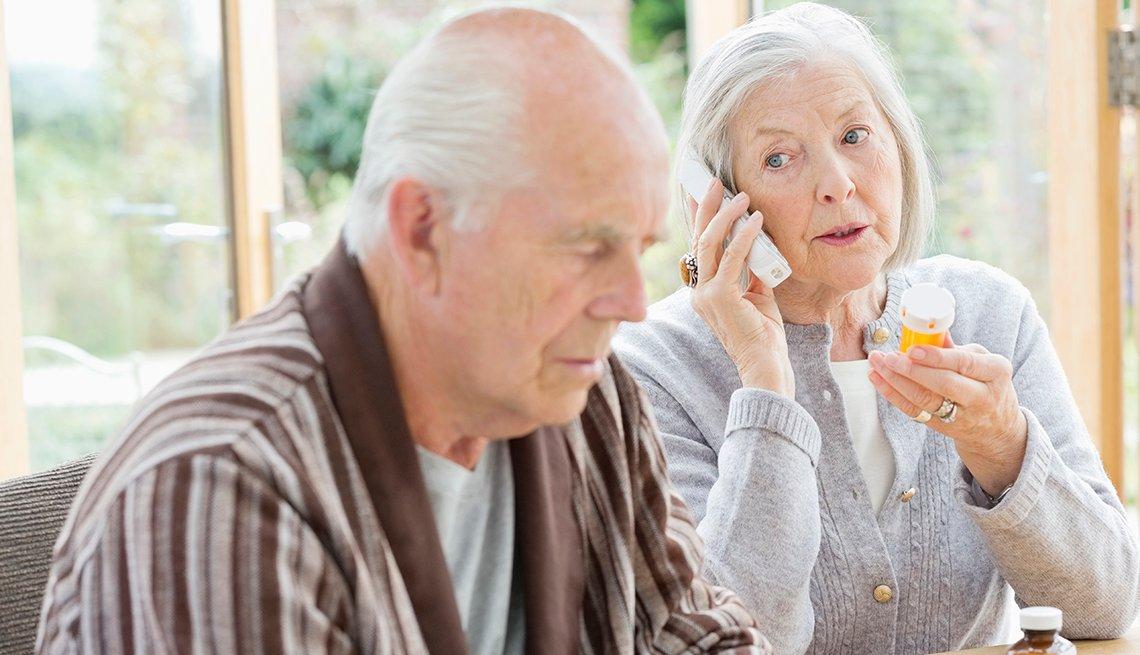 Mujer con un recipiente de medicamentos recetados en la mano habla por teléfono