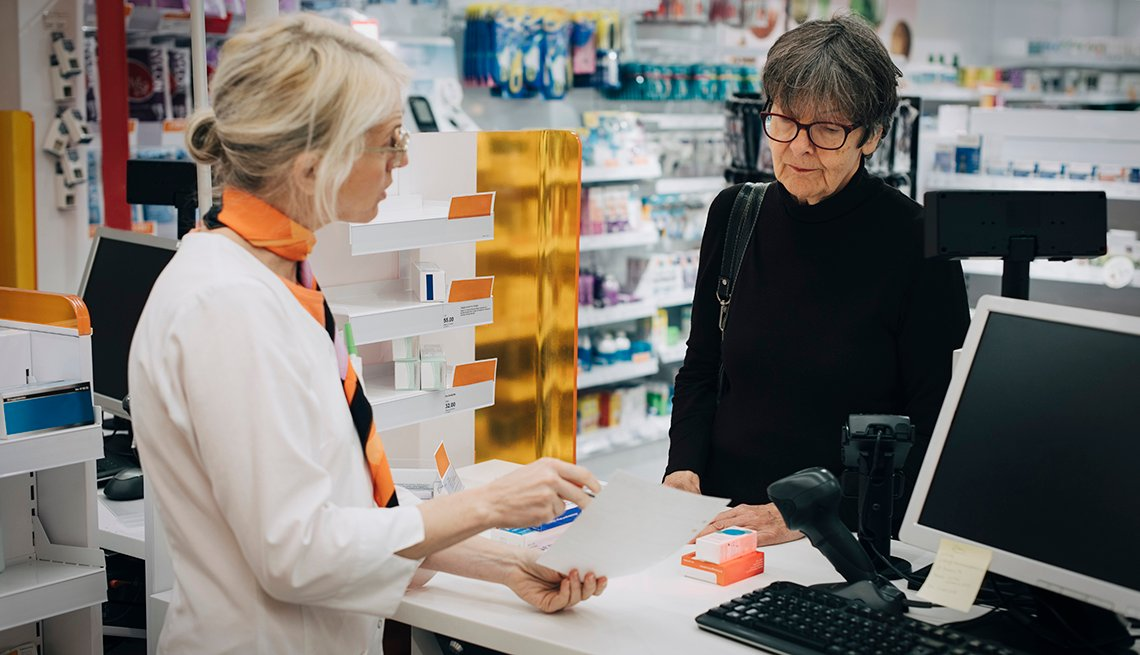 Woman at a pharmacy counter buying prescription drugs
