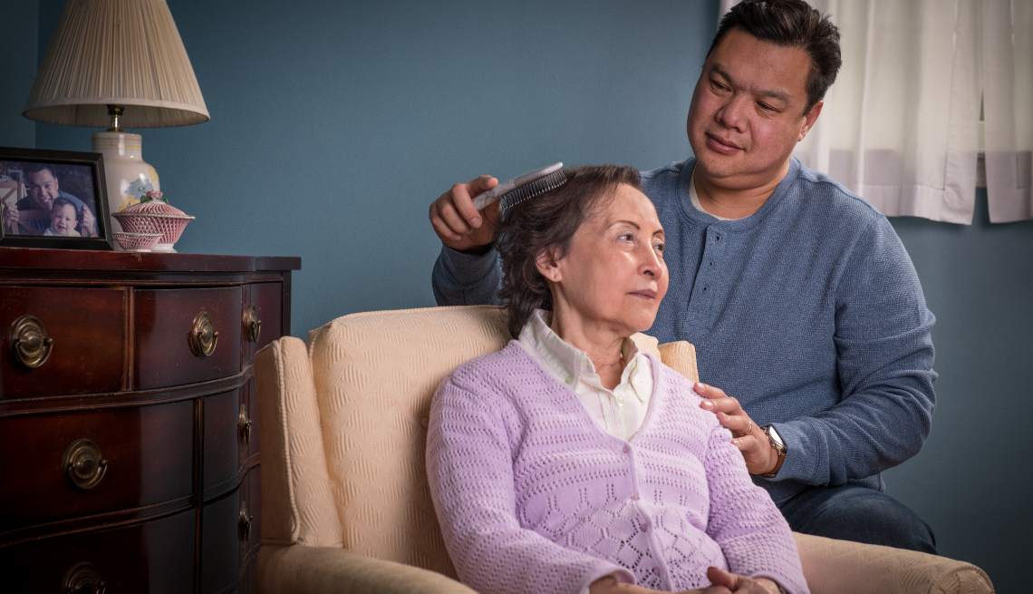 An adult son brushes his elderly mothers hair