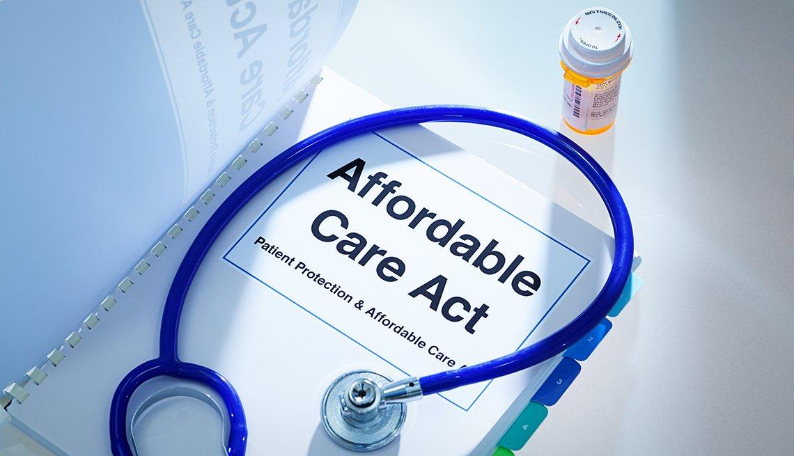 Un estetoscopio sobre un manual de la ley ACA y una botella de medicamentos recetados