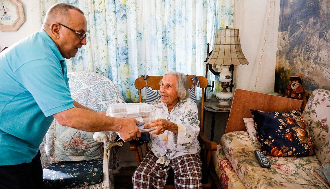 Hombre le entrega una caja con comida a una mujer anciana