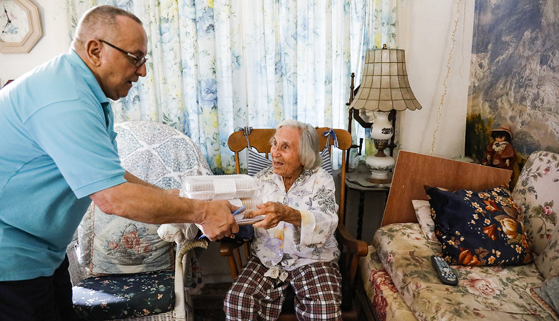 A man delivering a meal to an older woman