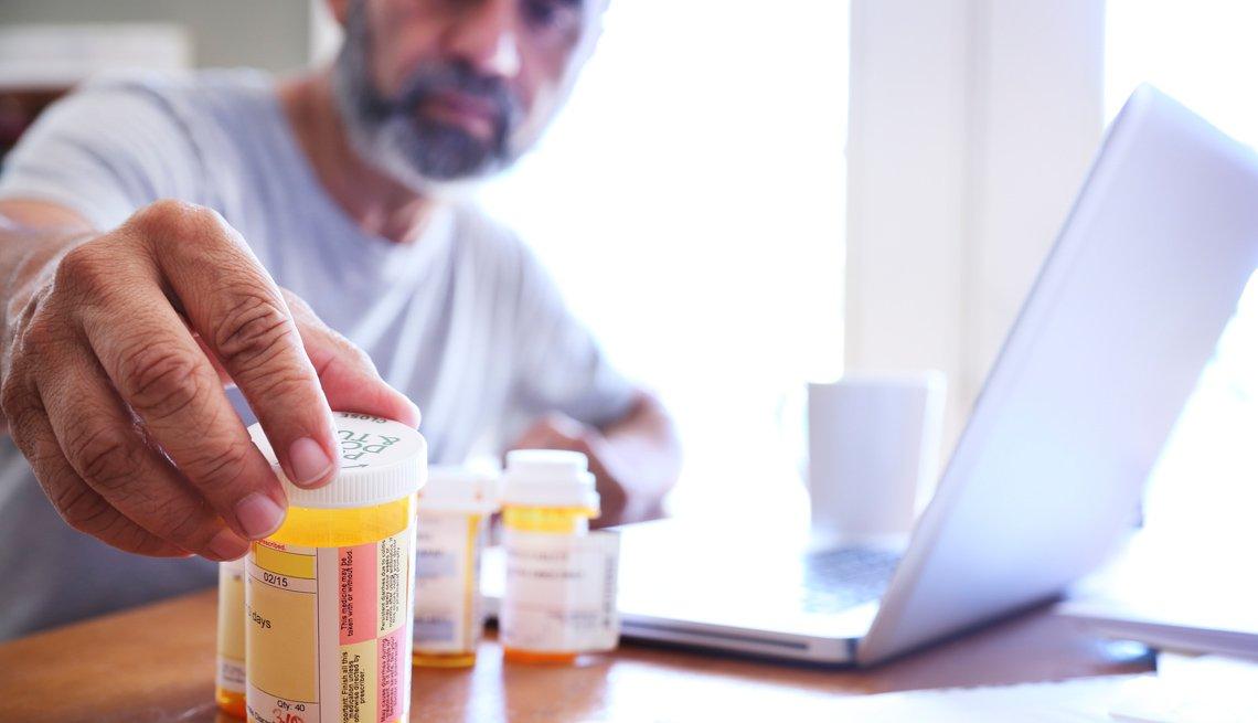 Hombre observa unos recipientes con medicamentos