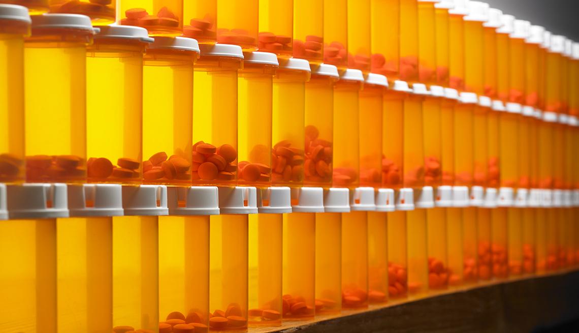 Frascos con pastillas de color naranja apilados en una pared