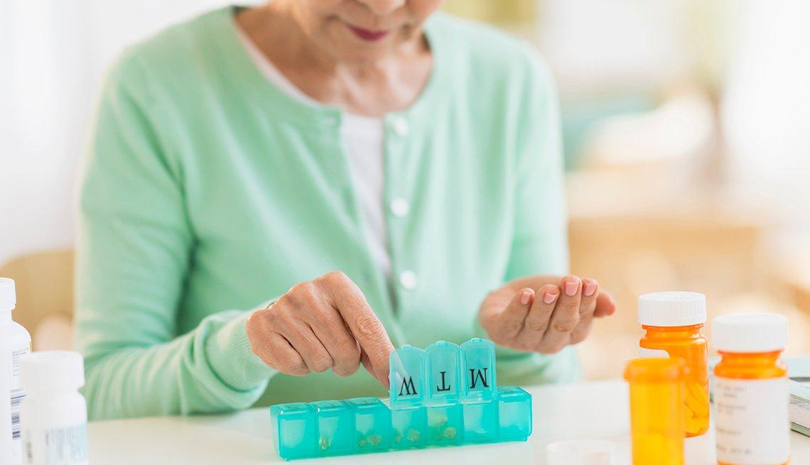 Mujer organiza pastillas de medicamentos recetados