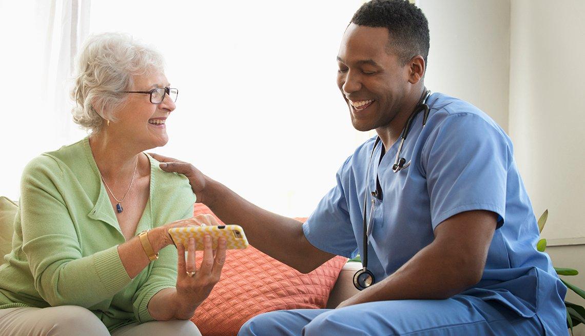 Enfermero sonríe con una paciente mayor