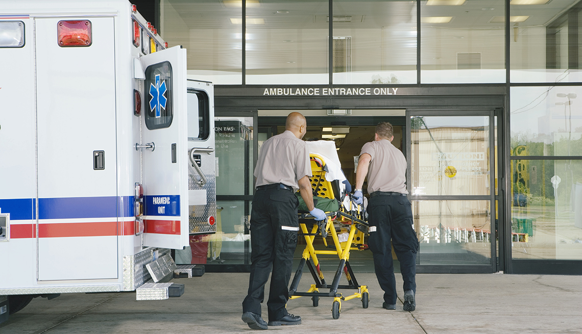patient on gurney being wheeled into hospital emergency room
