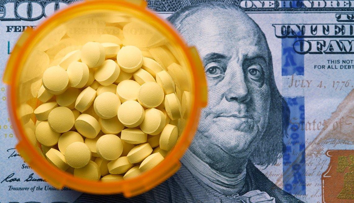 Recipiente con medicamentos sobre un billete de 100 dólares