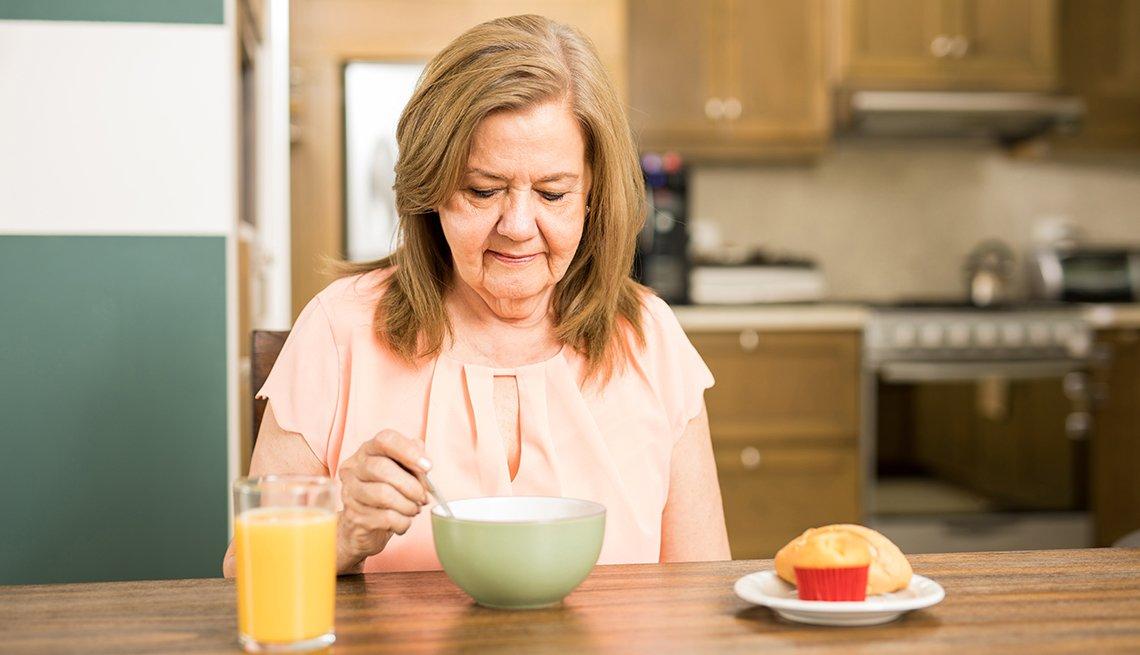 Mujer mayor come sus alimentos