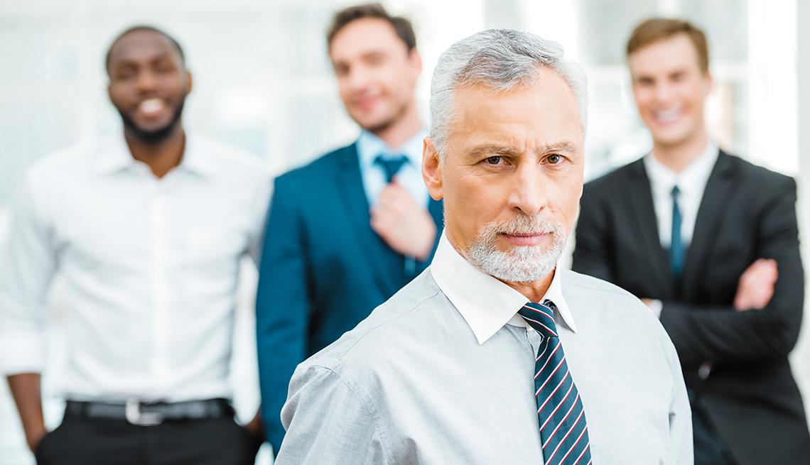 Hombre mayor parado frente a 3 trabajadores más jóvenes