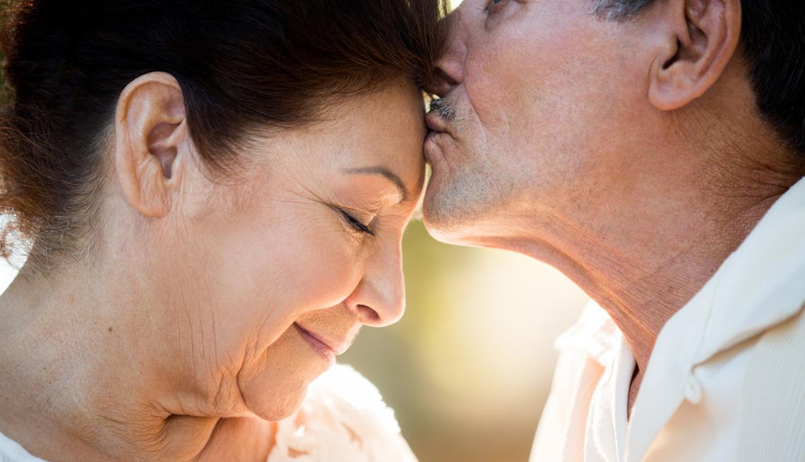 Hombre mayor besa en la frente a una mujer