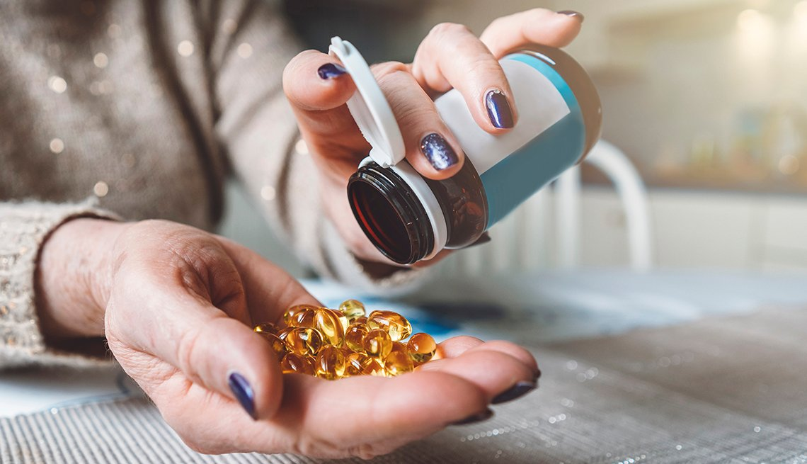 Woman emptying a pill bottle into her hand