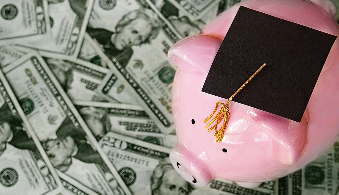 Alcancía sobre billetes de dólar con un birrete de graduación encima