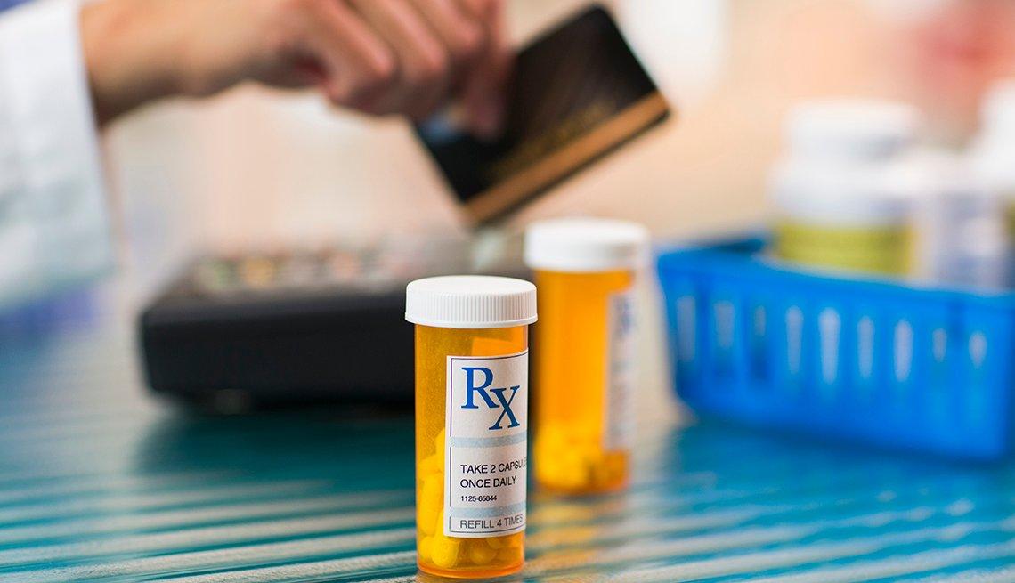 Frasco de medicamentos recetados y en el fondo una persona pagando con tarjeta de crédito
