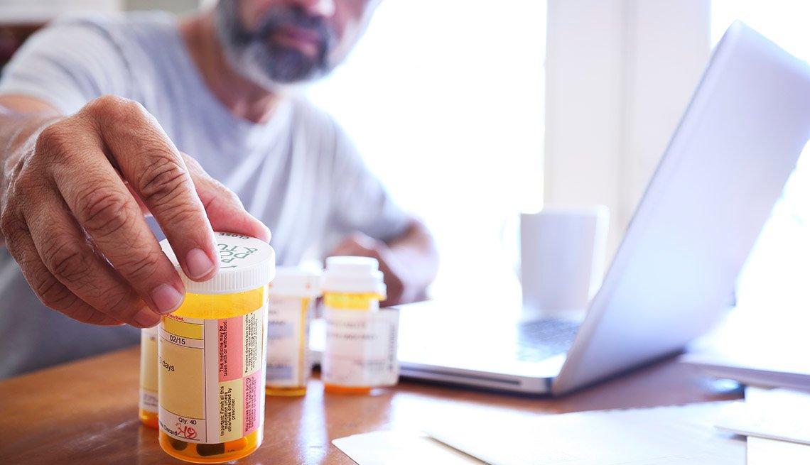 Un hombre adulto mayor alcanza uno de sus recipientes con medicamentos recetados