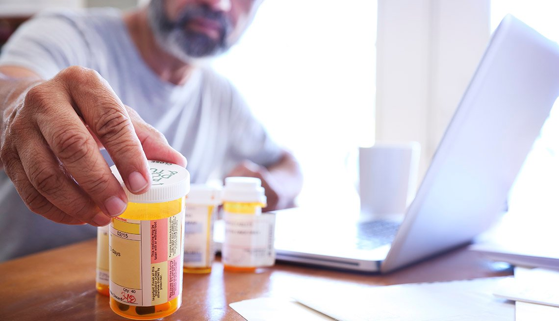 A Hispanic man in his late fifties reaches for one of his prescription medication bottles as he sits at his dining room table.  His laptop computer is open in front of him while sunlight filters in through the window behind him bathing the room with a sof