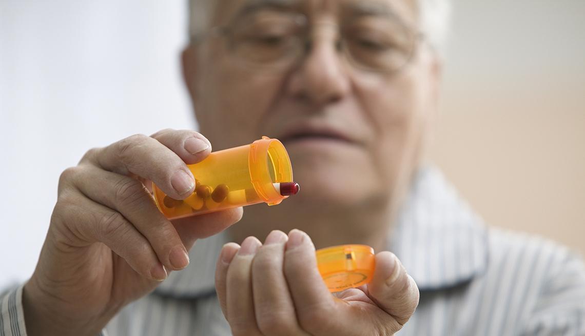 Hombre mayor preparándose para tomar su medicamento