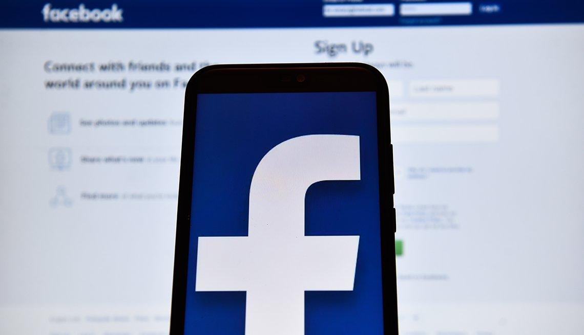 Logo de Facebook en la pantalla de un iPhone y un computador