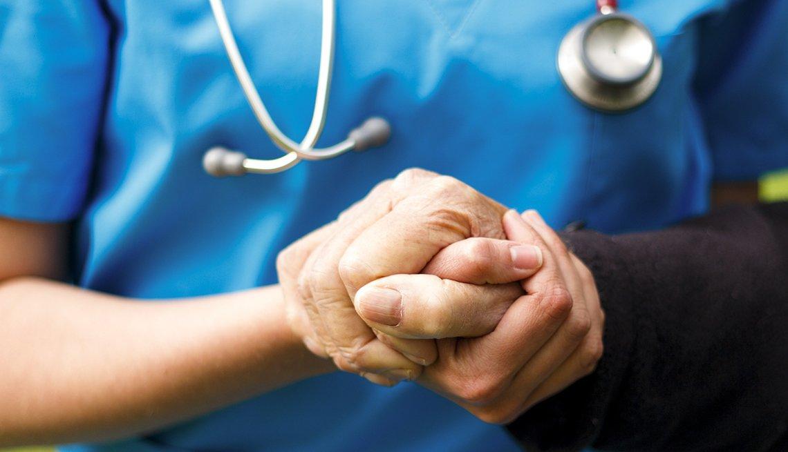 Doctor sostiene la mano de un paciente