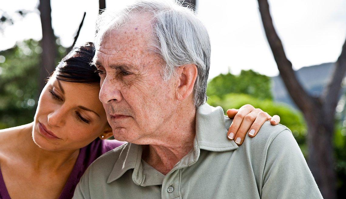 Mujer pone su brazo alrededor de un hombre mayor