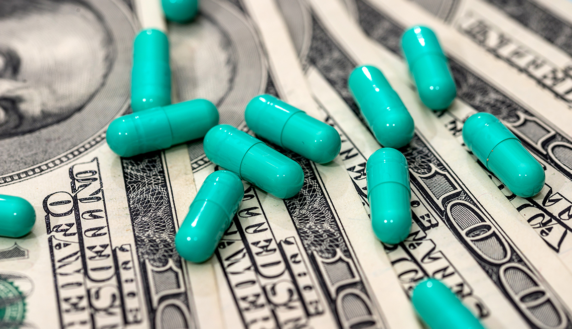 Green colored pills on a stack of money