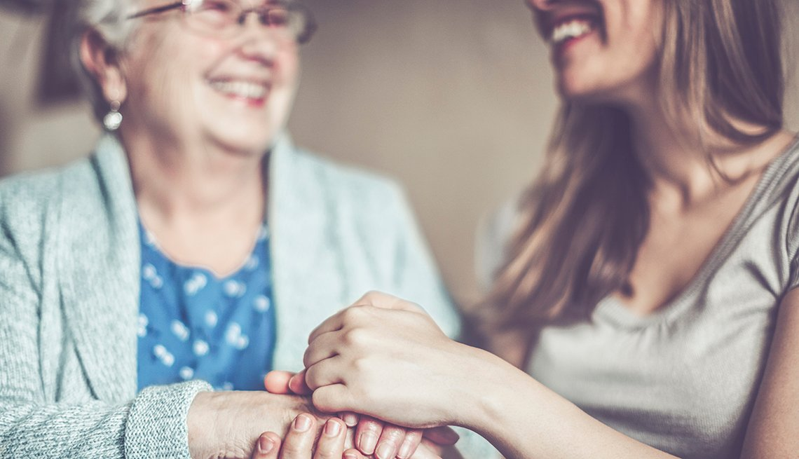 Woman holding her mother's hands and smiling