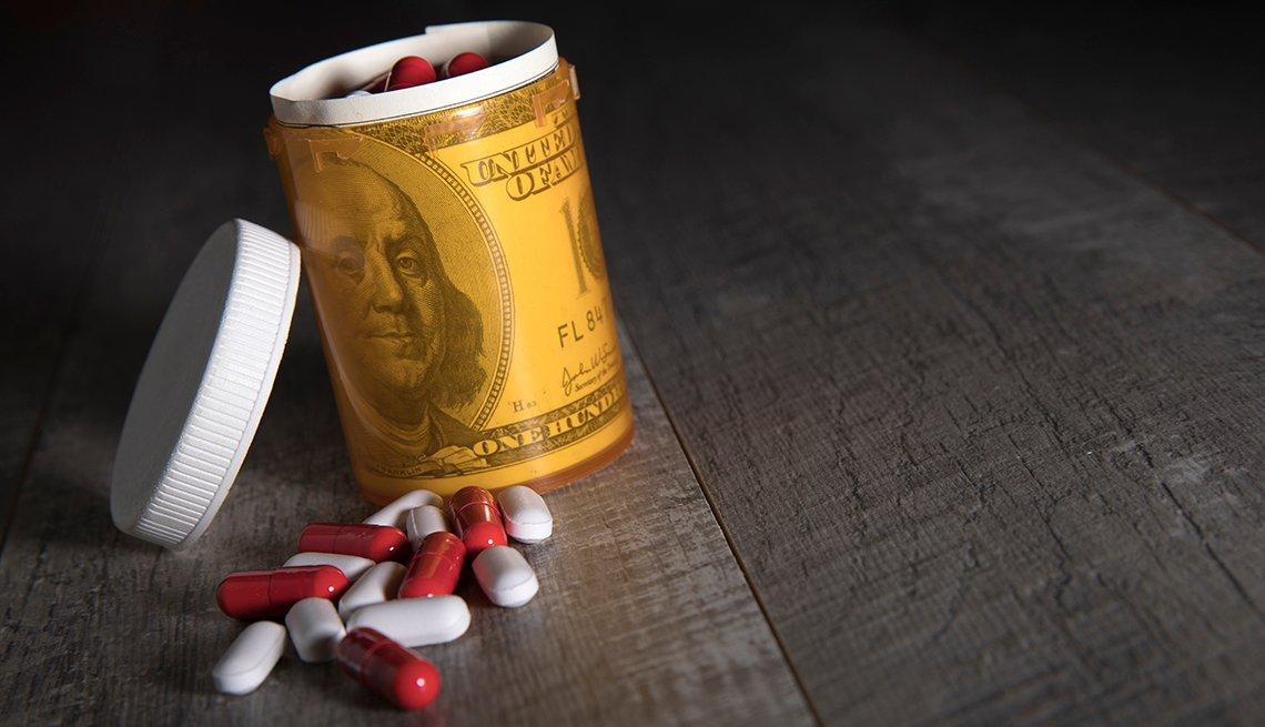 Cápsulas de medicina sobre una mesa al lado de un recipiente de pastillas envueltas en un billete de cien dólares