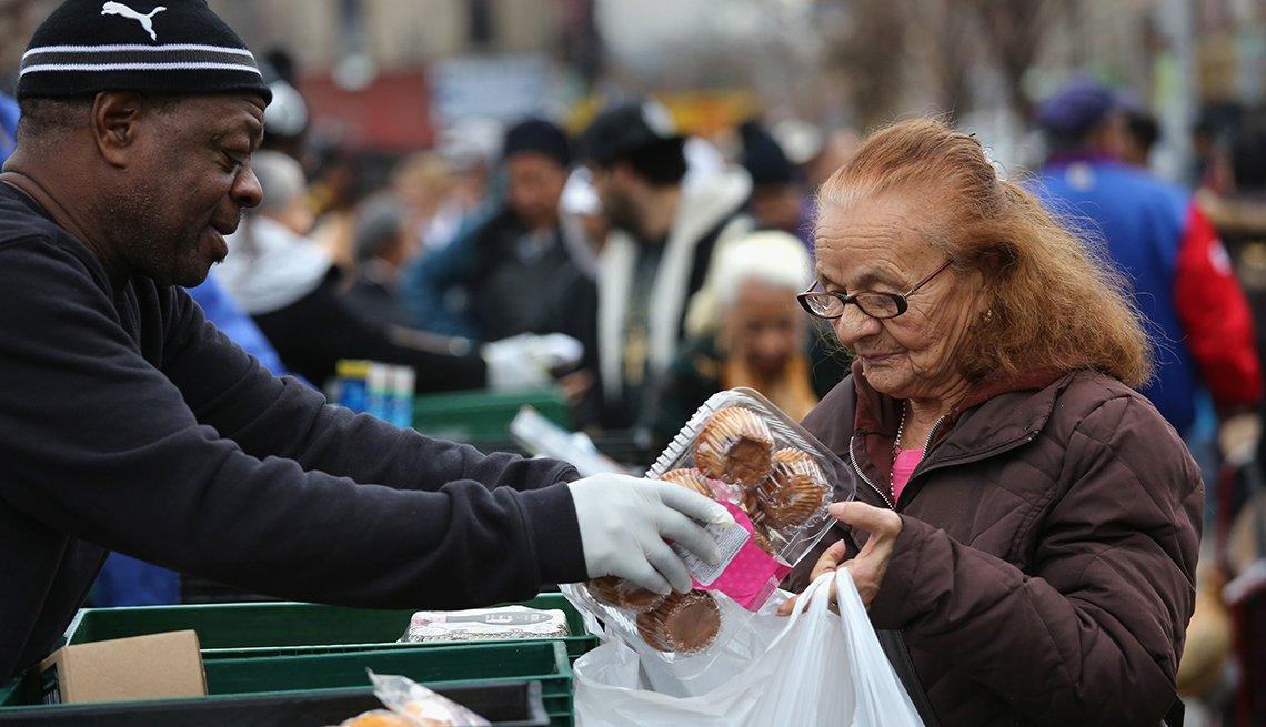 Mujer mayor recibe víveres gratis en un mercado