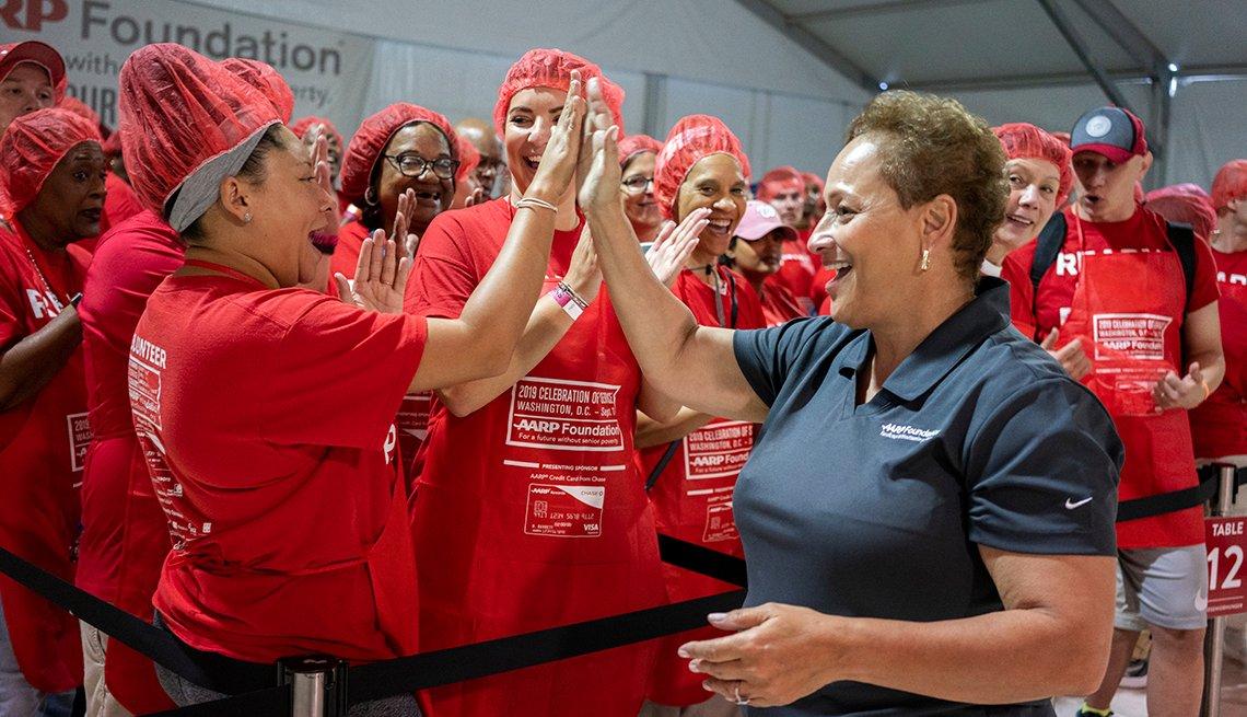 La directora ejecutiva de AARP, Jo Ann Jenkins, saluda a un grupo de voluntarios