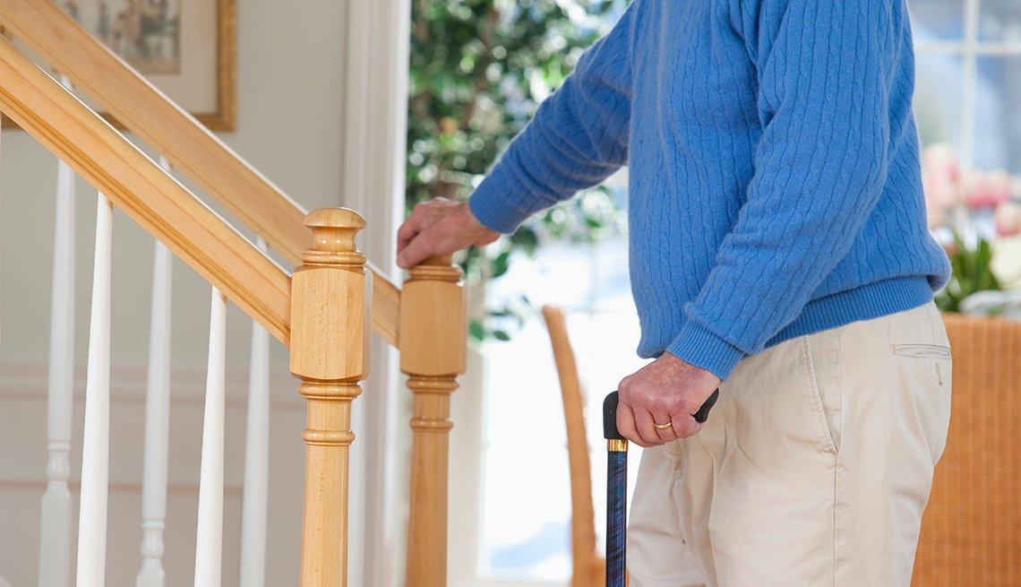 Hombre en un suéter azul está parado frente a las escaleras