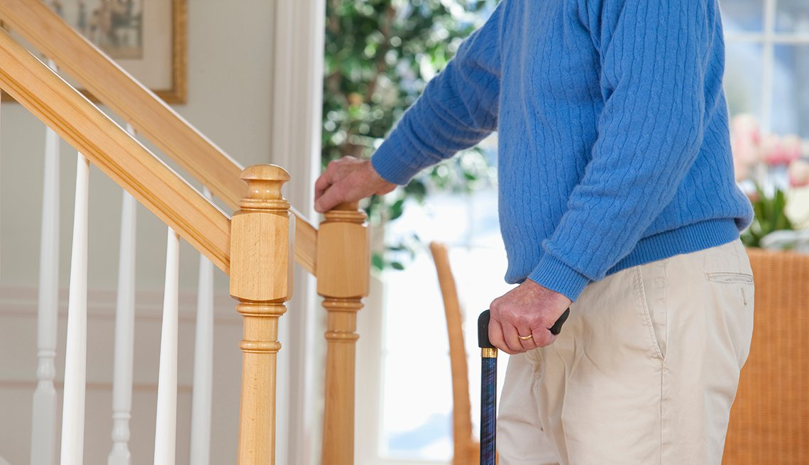 Man in a blue sweater stands in front of stairs while holding a cane