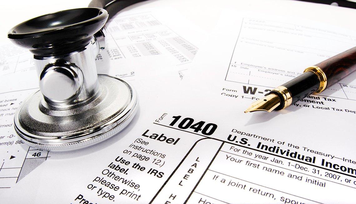 Formularios de impuestos con un bolígrafo y un estetoscopio