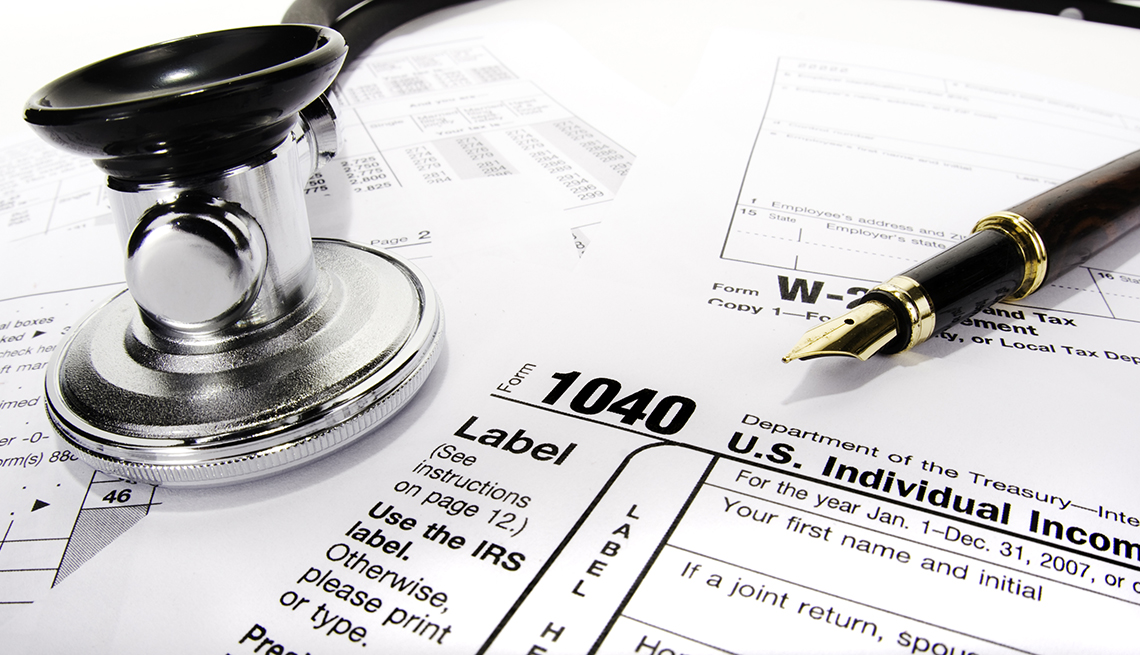 Tax forms with a pen and a stethoscope